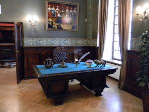 Duże zabytkowe biurko z piórem i inkaustem, w tle dawny obraz